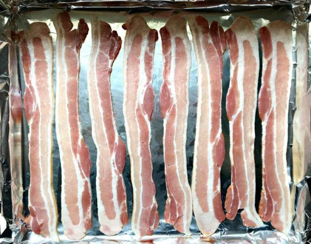 8 raw slices of bacon on a foil-lined baking sheet to make bacon for a crowd