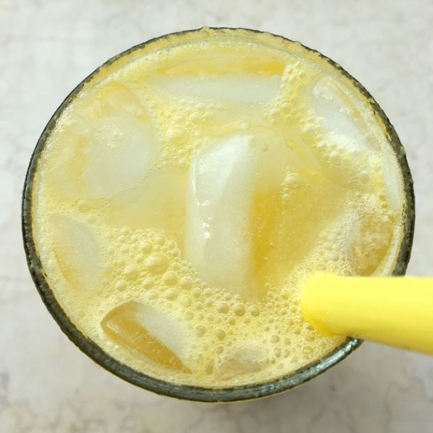 Looking down into a glass containing a yellow straw, ice cubes, and a yellow fruit sparkler drink
