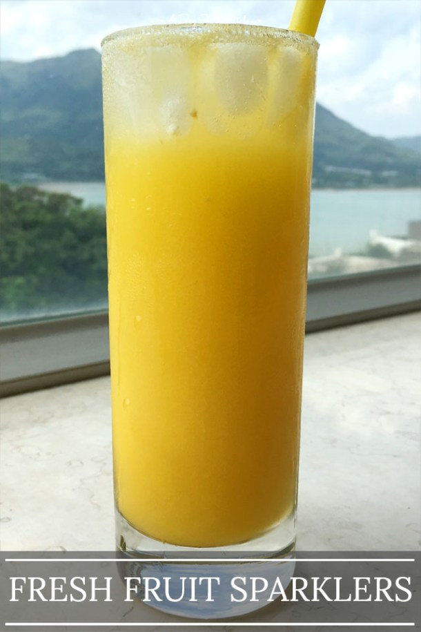 A tall glass by a window, containing a yellow liquid, ice cubes, and a yellow straw; the words fresh fruit sparklers at the bottom