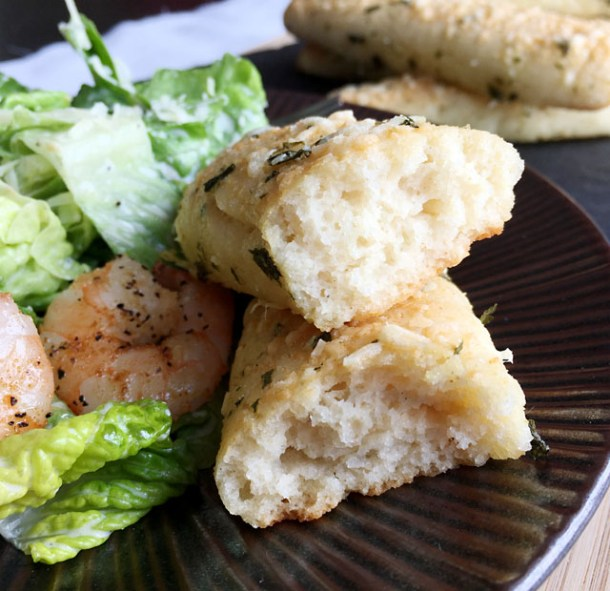 A breadstick ripped in half next to a green salad and pink shrimp on a brown plate