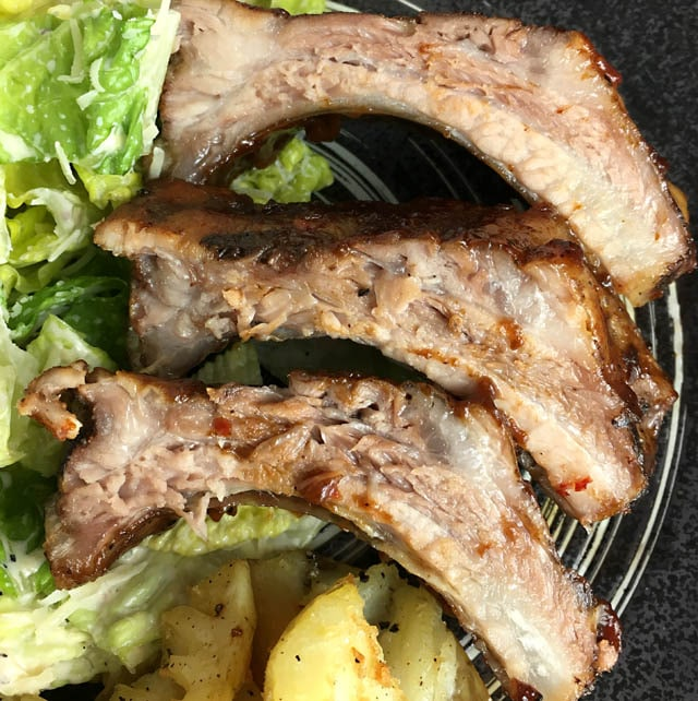 Three pork ribs on a dark plate containing green salad and yellow potatoes