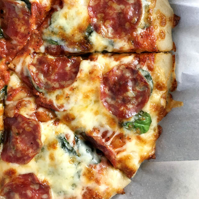 Cut slices of pan pizza in a parchment paper-lined pan