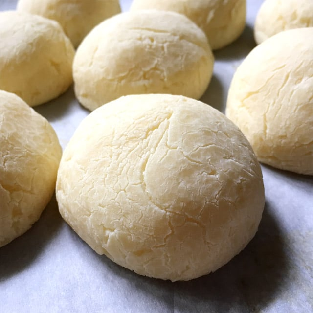 Several round baked cheese balls on parchment paper