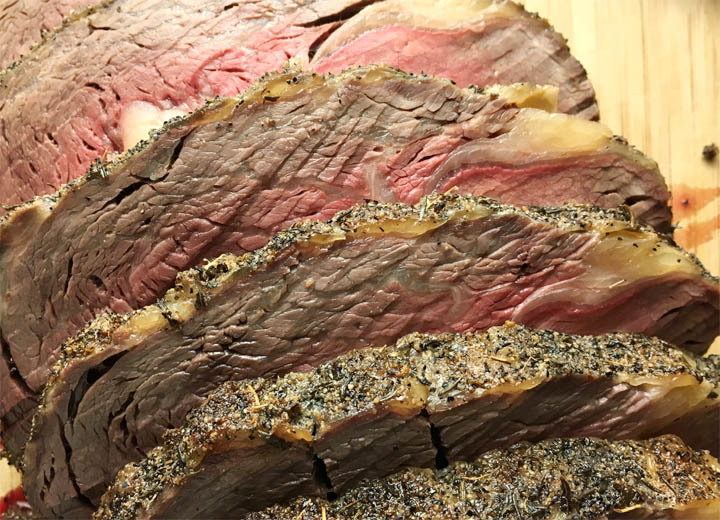 Slices of a beef roast on a wooden cutting board