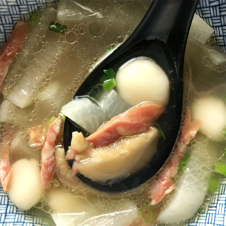 A black spoon containing a white dough ball, sausage strip, mushroom slice, and radish in soup