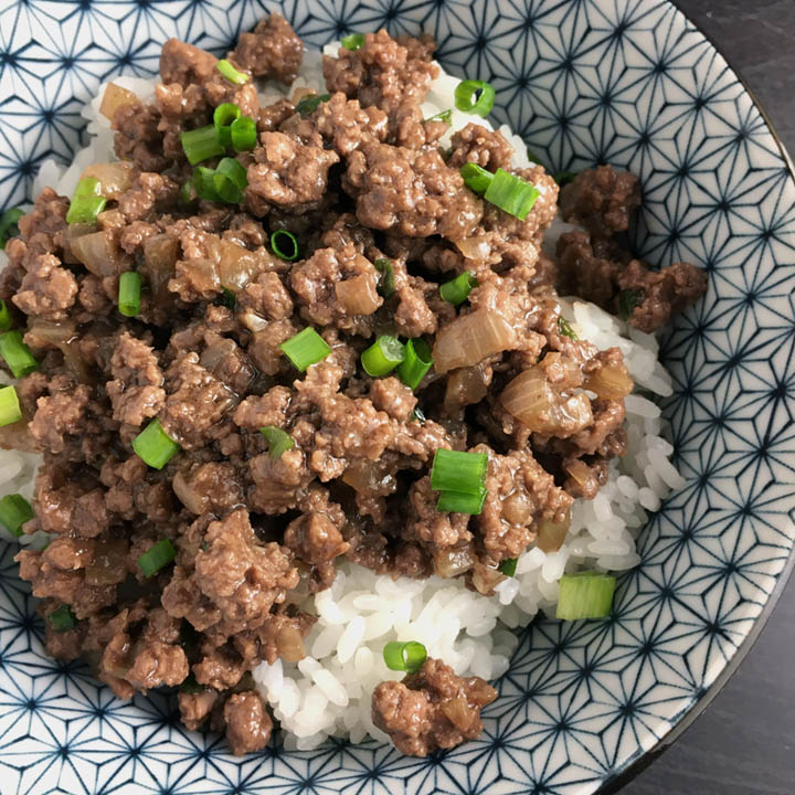 Closeup of saucy brown ground beef and chopped green onions on white rice in a round blue and white bowl