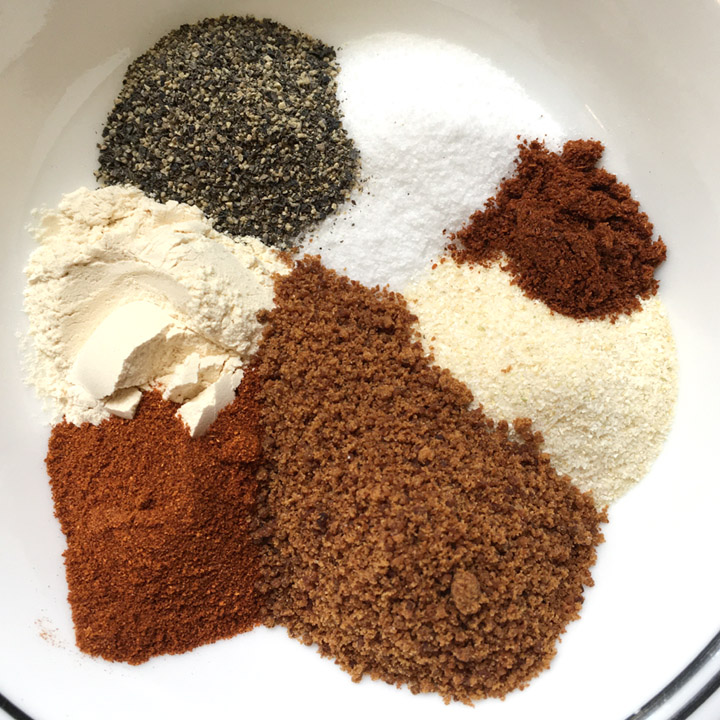A white bowl containing white, black, brown, orange, and yellow spices