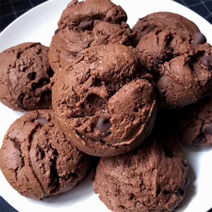 A round white plate containing several brown chocolate chip cookies