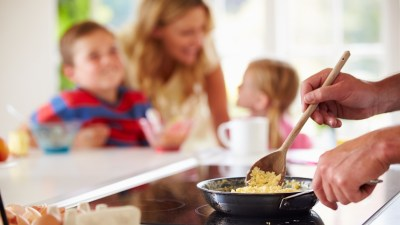 Father preparing scrambled egg breakfast for ADHD children