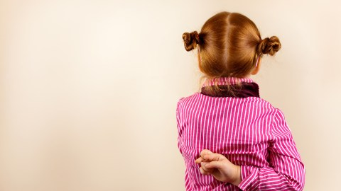 A child with ADHD crosses her fingers behind her back as she tells a lie.