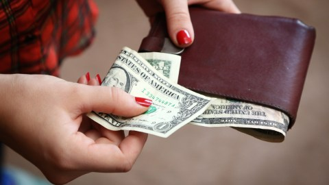 A woman takes cash out of her wallet and realizes she's been spending too much money.