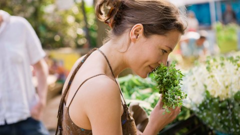 A woman with ADHD smelling herbs at a farmer's market