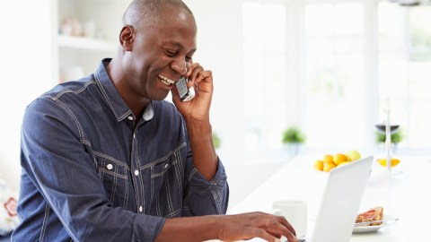 A parent on the phone with a teacher, working together