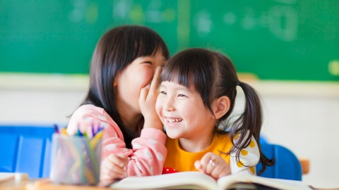 A girl with ADHD whispers a secret to her friend in class