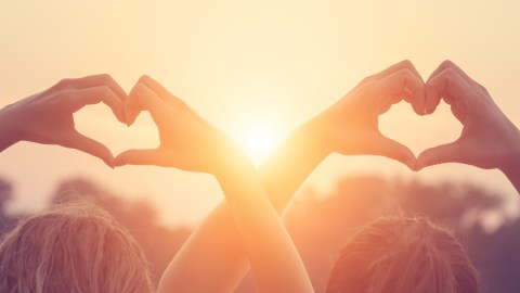 Two women with ADHD make hearts with their hands over their heads, a reminder to stay strong when you feel like you don't have any friends.