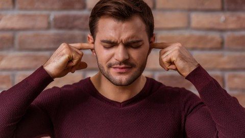 A man tries to tune out his ADHD emotions by plugging his ears.