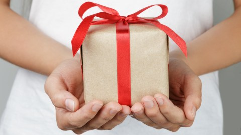 A woman with ADHD holds a gift.