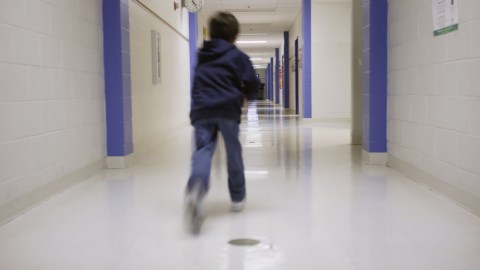 A boy with ADHD runs down a school hallway to expend energy