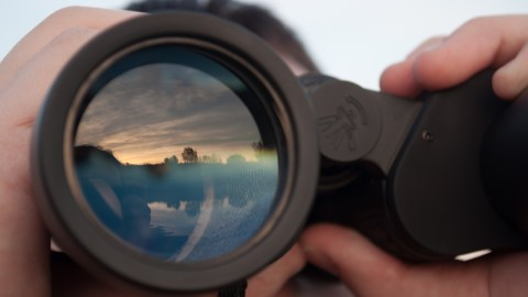 A man looks through a set of binoculars and thinks about what it feels like to have ADHD