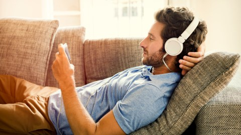 A man listening to white noise using headphones when he can't sleep.