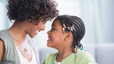 A mother uses positive parenting and smiles at her daughter with ADHD.