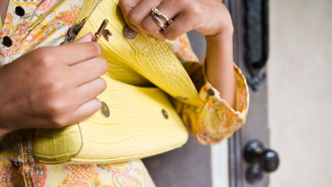 A woman putting her key in her purse to avoid feeling overwhelmed later