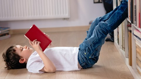 Young boy laying on his back during the summer, reading a book to prevent learning loss