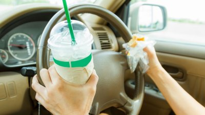 Close up of steering wheel of car being driven by ADHD person simultaneously holding a donut and a big gulp