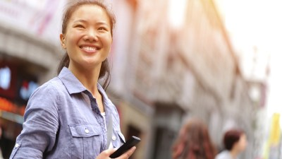 Woman with ADHD, on city street, smiling and holding cellphone after using to-do list app for organization