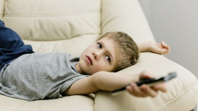 Boy with ADHD laying on couch and pointing remote control at screen while watching TV