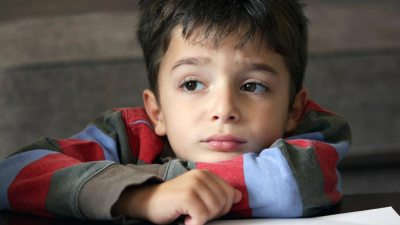 Sad little boy with ADHD sitting at desk