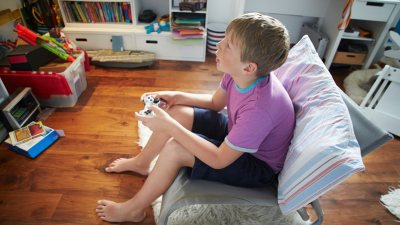 A blond boy playing video games to help with ADHD symptoms