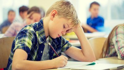 Young boy with ADHD taking test in classroom filled with students