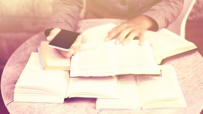 Student with ADHD and pile of books on table studying while holding cell phone