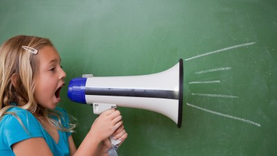 A young girl with ADHD yelling and acting impulsive in class, using a megaphone