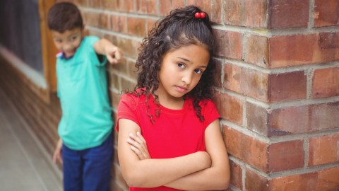 Upset ADHD child being teased by another child on the elementary school grounds