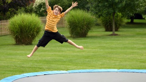 ADHD boy jumping on a trampoline to help him focus on homework