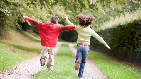 Two ADHD young friends running on a path outdoors to help them focus on homework.