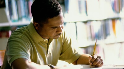 A man is very focused on writing in his notebook. Hyperfocus is a positive trait of ADHD, but adults with ADHD can also suffer from dysgraphia in adults.