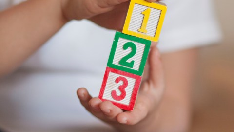A child with ADHD holds 1,2,3 stacked blocks - close up