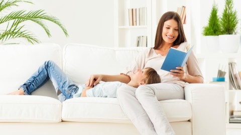 A mom reads a book about executive function to her daughter laying in her lap on the couch
