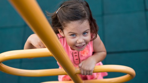 A girl with SPD climbs a chute at the playground.
