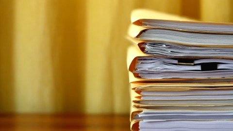 Manila file folders stacked on a desk. Keeping papers neat is an organization hack that always works.