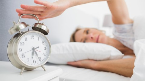 Tired woman turns off alarm she set to stay on task and on time.