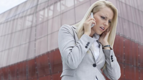 Woman with ADHD listening to someone on cell phone and getting angry in front of tall building