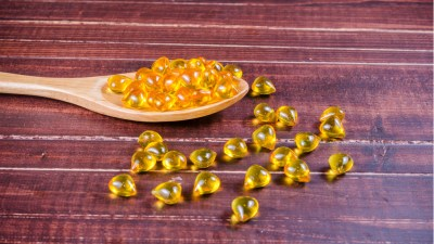 Fish oil tablets in wooden spoon are a good source of omega-3 for people with ADHD