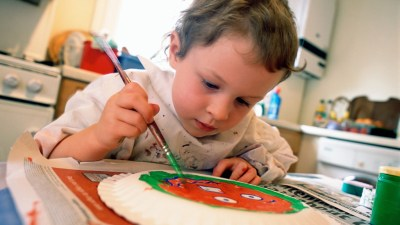 Boy with ADHD painting at the kitchen table