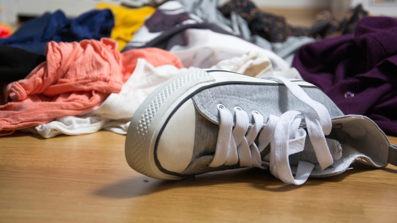 A messy floor covered in clothes that can't fit in a shared closet