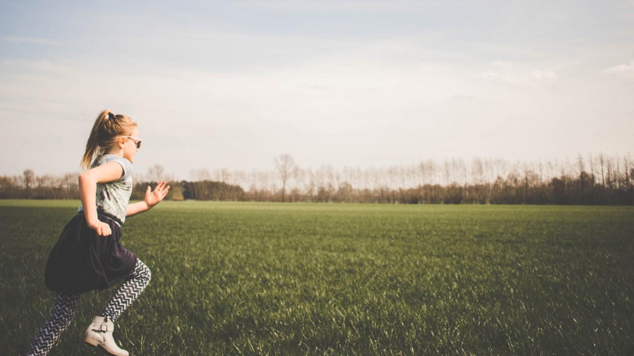 Girl running outside in the grass