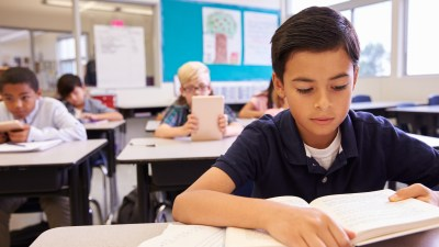 ADHD Schoolboy reading at his desk in an elementary school class